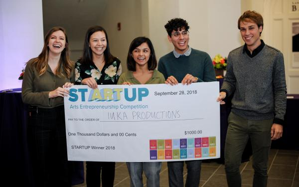 Iuka Productions student group, posing behind the $1,000 check they won at the StARTup competition at the 2018 Barnett Symposium. StARTup is Ohio State's first arts entrepreneurship competition.