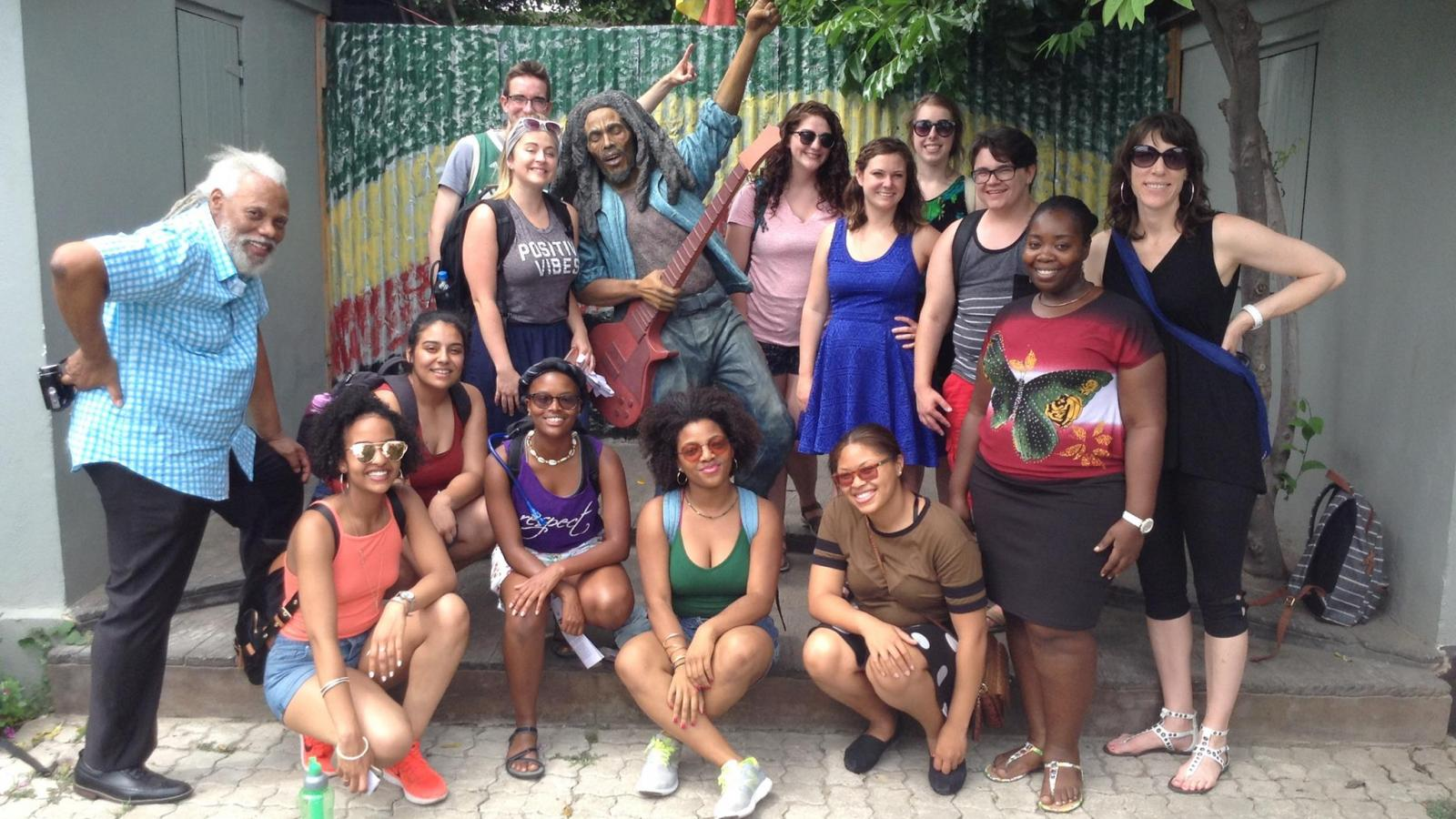 "ARTEDUC 5797.02 Exploring Jamaican Arts and Culture study abroad students pose with reggae musician and music educator Michael ""Ibo"" Cooper (left) at Trench Town Culture Yard, Kingston, Jamaica."