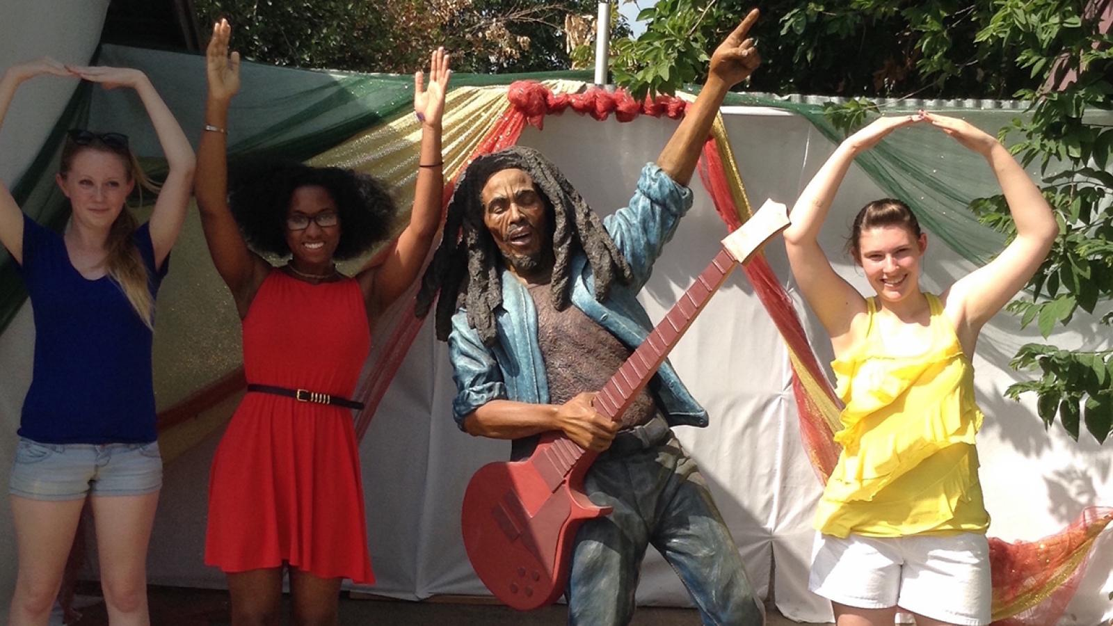 Students pose with a statue of Bob Marley in Kingston, Jamaica